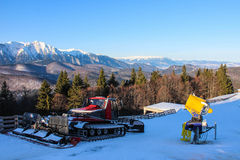 Snow Groomer, Snow Cannon and Mountain Landscape. A tracked vehicle used for impacting the surface of a skiing slope right next to a snow cannon on the clabucet Royalty Free Stock Photo