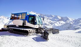 Snow grooming machine on snow hill ready for skiing slope preparations in Alps, Europe ski resort. ю Stock Image