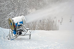 Snow gun (pulverizer) disperse artifitial snow on mountain,. Seasonal environment details Stock Photo