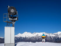Snow Gun and snowboarder woman in mountains. Snow machine gun and snowboarder woman standing at the edge of the slope and admiring mountain scenery of the Stock Images