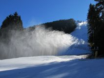 Snow gun spraying snow on the track in the forest in the morning. stock image