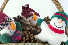 Snow guys in a basket. A festive basket filled with funny snowmen and pine-cones royalty free stock photos