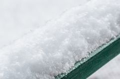 Snow on a handrail in cold winter day.  stock photography