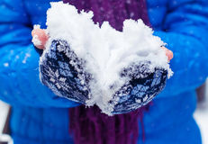 Snow in the hands of a young girl. Child Hands in mittens with fresh snow. Royalty Free Stock Images