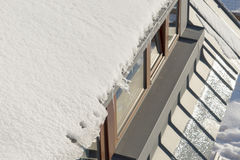 Snow hanging on the roof Stock Image