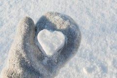 Snow heart in hand Stock Photos