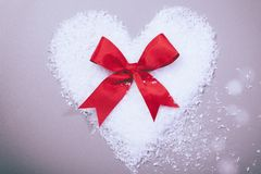 Snow heart with red ribbon loop Stock Photo