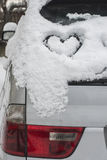 Snow heart shape on car. Close up Royalty Free Stock Photography