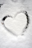 Snow heart shape view. Drawing heart in the winter snow closeup Stock Photo