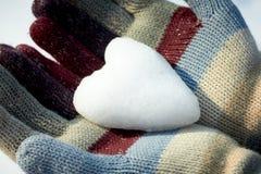 Snow heart in woman hands. Closeup Stock Photos