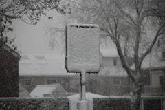 Snow is hiding a sign of busstop in the Netherlands. On a winter dayn Stock Image