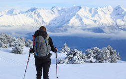 Snow hike. Female hiker on snowshoes in the snow covered mountains in France during a microadventure Stock Photography