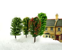 Snow At Home. Studio image of a domestic winter scene with deep snow. Focus on the foreground trees, defocussed property in the background. Copy space royalty free stock photo