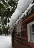 Snow and Ice Buildup on Cabin Roof. Alternating freezing and thawing weather can cause snow and ice buildup on roofs which may be hazardous or even cause water Stock Photography
