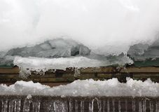 Snow and Ice Buildup on Roof. A close up image that shows snow and ice build up on a roof as a result of freezing and thawing winter weather conditions.  Snow Stock Photo