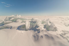 Snow, ice, hummocks on snow-covered ice of lake. Royalty Free Stock Photos
