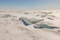 Snow, ice, hummocks on snow-covered ice of lake. Stock Photo