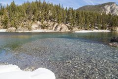 Snow and ice malting Bow River Banff Alberta Canada stock photos