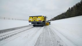 Snow and ice removal truck removes snow from the road with big bucket and rotating brush in snowy weather, special. Machinery for roads cleaning, snow and ice stock footage