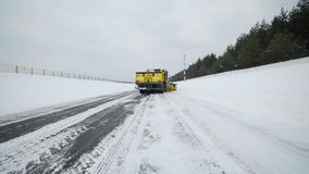 Snow and ice removal truck removes snow from the road with big bucket in snowy weather, special machinery for roads. Cleaning, snow and ice removal, specialized stock video