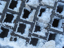 Snow and Ice on Square Grate Royalty Free Stock Photography