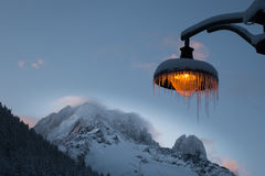 Snow and icicle covered amber lightpost against backdrop of wind Royalty Free Stock Images