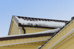 Snow and icicles on the roof Stock Photo