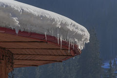 Snow with icicles on roof. Of house Royalty Free Stock Photos