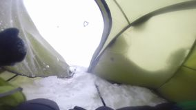 Snow invaded a tent. A shot from inside a tent where snow has already came inside the tent stock video