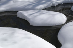 Snow Island in Creek. After an overnight snowstorm snow has stacked up on the rocks and ice of a small creek, creating islands of snow Royalty Free Stock Images