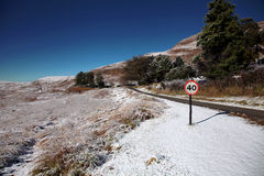Snow Landscape With Speed Limit Sign. Snow covered hills surrounding a small road, with a speed limit warning placed next to it royalty free stock photos