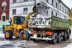 Snow loading. Digger gives snow into the truck in winter Royalty Free Stock Photography