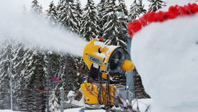 Snow machine gun on a ski slope and a snowman. Yellow snow cannon stands on a snowy mountain in the winter and works by producing a column of snow on the stock video footage