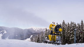 Snow machine gun on a ski slope. Timelapse. Yellow snow cannon stands on a snowy mountain in the winter and works by producing a column of snow on the background stock video