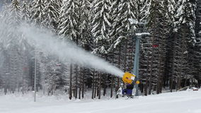 Snow machine gun on a ski slope. Yellow snow cannon stands on a snowy mountain in the winter and works by producing a column of snow on the background of stock footage
