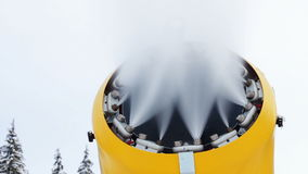 Snow machine gun on a ski slope. Yellow snow cannon stands on a snowy mountain in the winter and works by producing a column of snow on the background of stock video