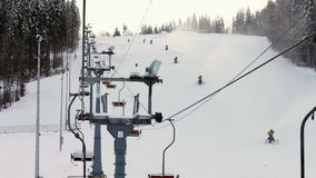 Snow machine gun on a ski slope. Yellow snow cannons stand on a snowy mountain in the winter and work by producing a column of snow on the background of stock video footage