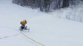 Snow machine gun on a ski slope. Yellow snow cannons stand on a snowy mountain in the winter and work by producing a column of snow on the background of stock video