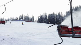 Snow machine gun on a ski slope. Yellow snow cannons stand on a snowy mountain in the winter and work by producing a column of snow on the background of stock footage