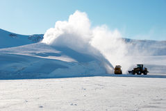 Snow machines. A snowblower and tractor cleaning a landing area stock image