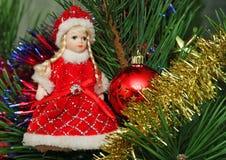 Snow Maidan and red ball on the Cristmas pine. Snow Maidan and red Cristmas ball and other decorations on the Cristmas pine Stock Photo