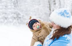 Snow maiden and baby boy embracing in a winter park amoung trees branches. Mother and little son in her arms. Happy family. Closeup portrait royalty free stock photo