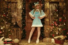 Snow Maiden on doorstep of house decorated in Christmas style Stock Photo