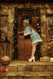 Snow Maiden on doorstep of house decorated in Christmas style try to open door Stock Photos