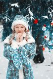 Snow Maiden in the forest. little girl froze over in winter. the child warms his hands. happy new year. Snow Maiden in the forest. little girl froze over in royalty free stock photo