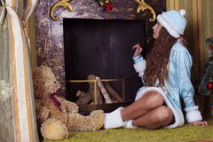 Snow-maiden looking into fireplace chimney. Teen girl in Snow-maiden costume looking into fireplace chimney stock photos