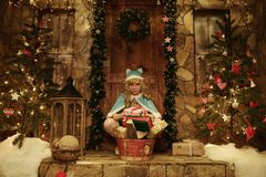 Snow Maiden with presents on doorstep of house decorated in Christmas style Royalty Free Stock Images