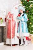 Snow maiden and santa claus. Posing near christmas fir stock images