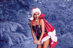 Snow maiden. Winter forest. Tale. The girl stands on a forest glade in the hat of Santa Claus. With gifts stock images