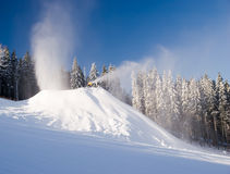 Snow makers in action. Snow guns and makers in action in winter on the snowy hill with forest in background Stock Photo